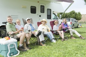 Happy Caucasian family sitting together in row on vacation with RV in the background